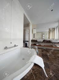 moderne badezimmer interieur mit doppel waschbecken und große spiegel badewanne fliesen sichtfenster und handtücher