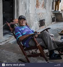 Senior Adult Male Cuban Man Relaxes Outside In Wooden Rocking Chair ... Indoor Wooden Rocking Chairs Cracker Barrel Old Country Store Fniture The Hot Bid Chair Benefits In The Age Of Work Coalesse Outdoor Two People Sitting 22 Popular Types To Make Your Home Stylish Fisher Price New Born To Toddler Rocker Review Best Baby Rockers Rated In Recling Patio Helpful Customer Reviews Amazoncom Gripper Nonslip Omega Jumbo Cushions 1950s 1960s Couple Man Woman Sitting On Porch In Rocking Chairs Most Comfortable And Recliners For Elderly Comforting Fictions Dementia Care New Yorker