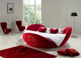 Red Heart Shaped Bed With Floor Lamp And Red Carpets And Pillows