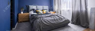 modernes kobaltblaues schlafzimmer mit doppelbett grauer bettwäsche teppich und fenster panorama