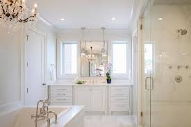 white master bathroom illuminated with chandelier over tub and