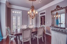 Victorian Inspired Dining Room With Hardwood Floors And A Chandelier On Purple