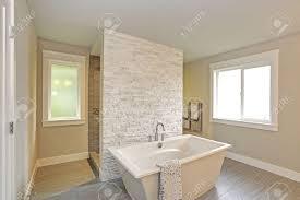 erstaunliches master badezimmer mit einer steinwand duschkabine und einer freistehenden badewanne über einem mit porzellan gefliesten boden