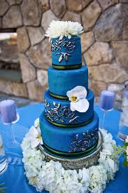 A beautiful rich blue wedding cake set over four tiers adorned with fresh white orchids on the tiers white dahlias on the top and surrounded by a base of
