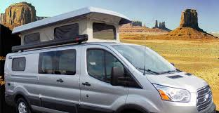 Side View Of A Custom Silver Sportsmobile Camper Conversion Van With The Penthouse Top Extended