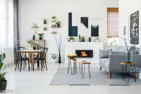 schwarze stühle am esstisch im hellen wohnzimmer interieur mit grauen sofa in der nähe kamin echtes foto stockfoto und mehr bilder biologie