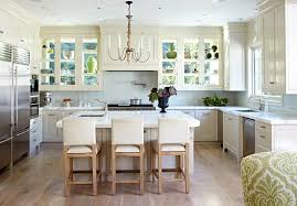 Of The Glass Doored Cabinets Allowing Light To Pour In And Illuminate Simple White Kitchen Calacatta Marble Counters A Bleached Wood Floor