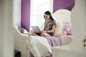 mädchen sitzen auf ihrem bett mit einem laptop computer foto monkeybusiness auf envato elements