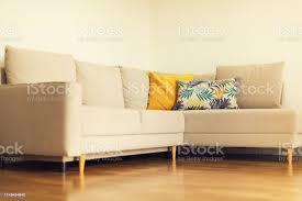modernes beiges sofa gelbe und blaue kissen mit tropischen palmen monsteramuster im wohnzimmer mit weißen wänden kopieren sie den innenraum design