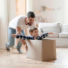 und vater spielen mit einer kiste im wohnzimmer