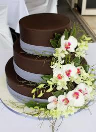 3 tier chocolate round wedding cake with fresh white flowers JPG