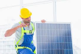 travailleur serrant le panneau solaire dans le bureau photo stock