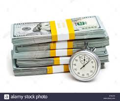 Time is money concept stopwatch and stack of new 100 US dollars