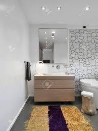 vordergrund holzmöbeln und gelben teppich im modernen badezimmer