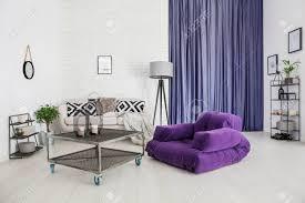 purpurroter lehnsessel nahe bei blauem tisch mit kerzen im hellen wohnzimmer mit vorhängen und le neben sofa