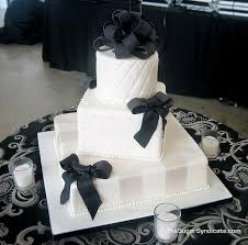 Very Elegant Round And Square Three Tiered White Wedding Cake Each Tier Is Dellicately Placed On An Angle Garnish With Black Fondant Bows