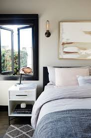 In This Modern Bedroom A Metallic Side Lamp Textured Rug And Black Bed Frame Windows Bring Sophistication Dimension To The Space