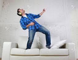 junge attraktive 20er oder 30er jahren menschen die spaß sprang auf der zu hause musik hören über handy mit kopfhörern tanzen singen und