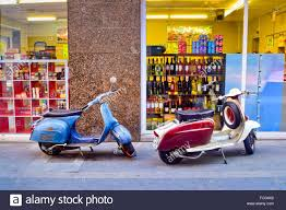 Two Vintage Vespa Scooters Parked In Front Of A Grocery Store Barcelona Catalonia Spain