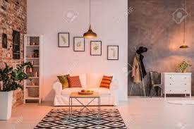 geräumiges wohnzimmer mit backsteinmauer tisch und le