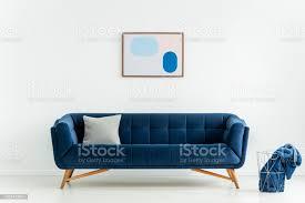 plakat über dem blauen sofa mit kissen in weiß wohnzimmer interieur mit decke im korb echtes foto stockfoto und mehr bilder blau