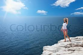 Young Woman Standing On Cliffs Edge And Looking To A Sea