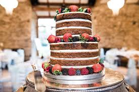 A Naked Wedding Cake Decorated With Fruit And Berries At The Luxury Venue In Buckinghamshire