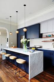 Modern Kitchen With Dark Blue Cabinents A Marble Island Pendant Lights And Wooden