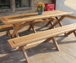 long outdoor wooden picnic table with detached benches and flower