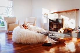 Mixed Race Girl Relaxing In Beanbag Chair Living Room