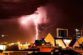 A Bright Bolt Of Lightning Emerging From Dark Purple Sky Over Buildings In Perths CBD