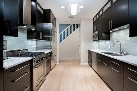 A Sleek Modern Kitchen Featuring Glass Tile Backsplash In Light Blue Gray Stainless