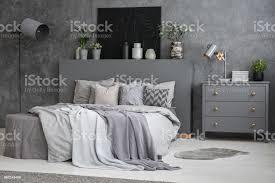 blätter auf bett zwischen schrank und le in grau schlafzimmer innenraum mit schwarz poster echtes foto stockfoto und mehr bilder beton