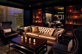 A Candlelit Space With Plush Seating And Windows Overlooking City At Night