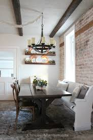 Farmhouse Chandelier Over Wood Table With Brick Wall And A White Pew