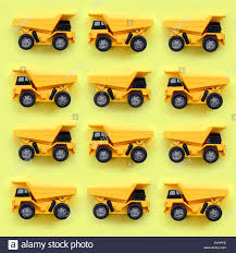 Many Small Yellow Toy Trucks On Texture Background Of Fashion Pastel ...