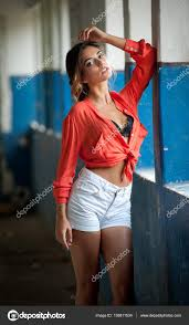 beautiful with red shirt and white shorts posing in old hall