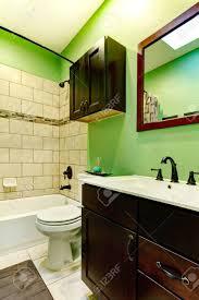 elegantes badezimmer mit grünen wand fliesen verzierte wand dunkelbraun bashbasin schrank mit weißen zähler nach oben