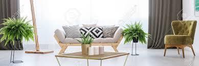 helles natürliches wohnzimmer mit grünem lehnsessel anlagen und kerzen auf metallcouchtisch