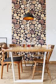 hölzerner speisetisch stühle und wanddekoration im modernen hellen esszimmer mit natürlichem design