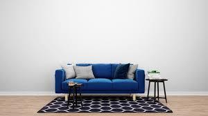 minimales wohnzimmer mit blauem sofa und teppich