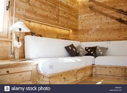 alpine wohnung wohnzimmer mit weißen sofa und holzwand im