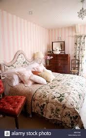 rosa gestreifte tapete im land schlafzimmer mit blumen quilt