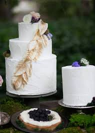 White Wedding Cake With Golden Leaves And Wood Grain Etchings