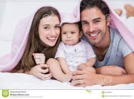 Portrait Smiling Couple With Baby Bed Stock Image