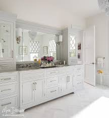 pale gray bath vanity cabinets with white marble herringbone tile