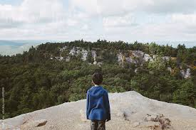 Boy Stands Near Cliff Edge Looking Out At Tree Covered Mountains By Kelli Kim For Stocksy