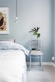 Serene Blue Bedroom With A Chair Doubling As Nightstand And Hanging Pendant Light