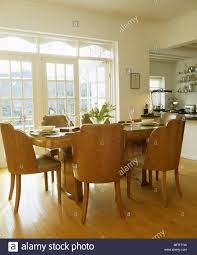 Dining Area Of Kitchen With French Windows And Art Deco Style Table Chairs