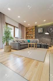 helles wohnzimmer mit parkett hintergrundbeleuchtung fenster bücherregale und mit couchtisch in der mitte